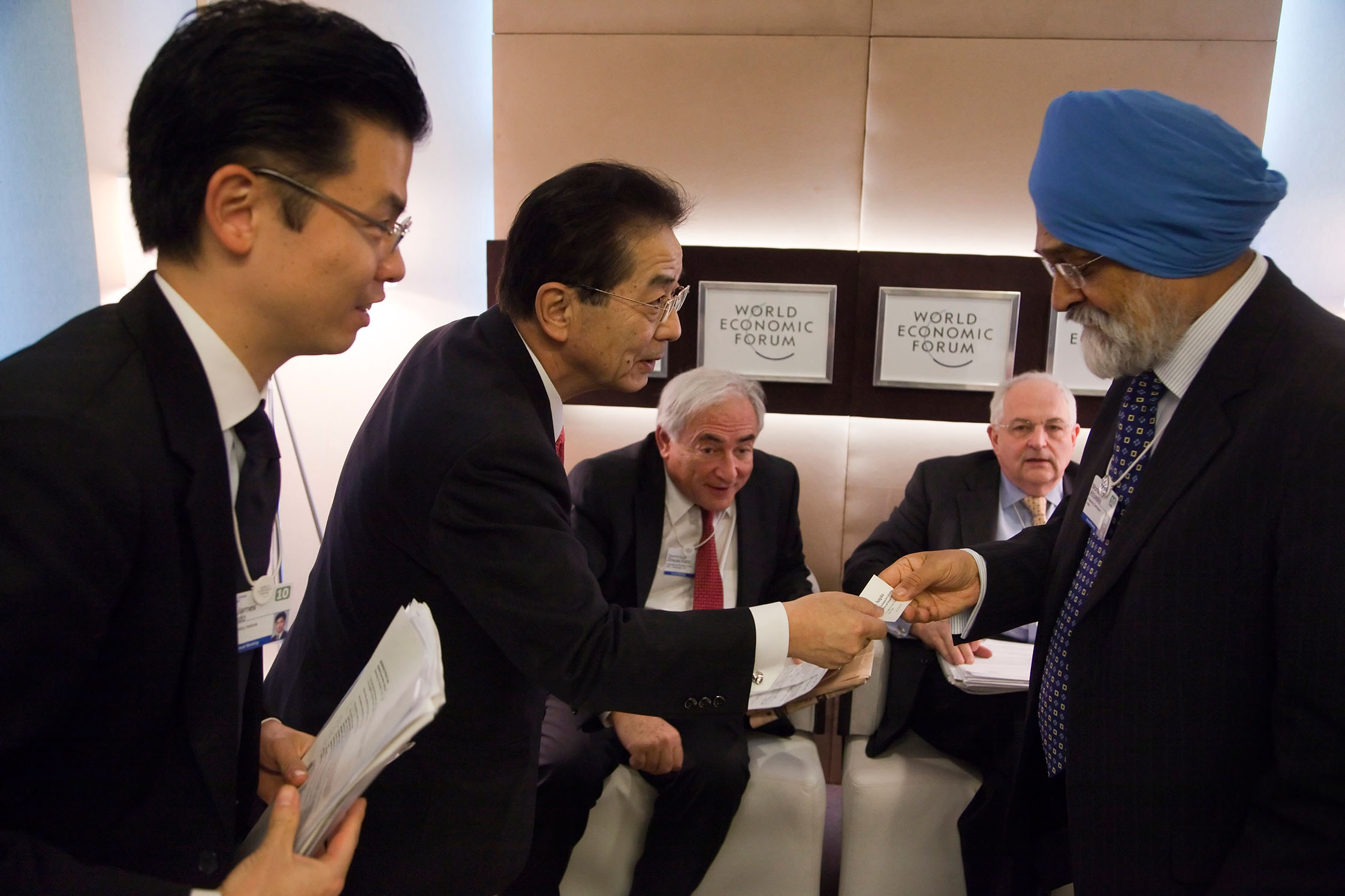 Yoshito SENGOKU, Japanese Minister for National Policy, giving his business card to Montek AHLUWALIA, Deputy Chairman of the India Planning Commission. IMF Managing Director Dominique STRAUSS-KAHN and Financial Times editor Martin WOLF look on.